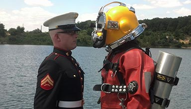 A service member in uniform and a commercial diver stand facing each other